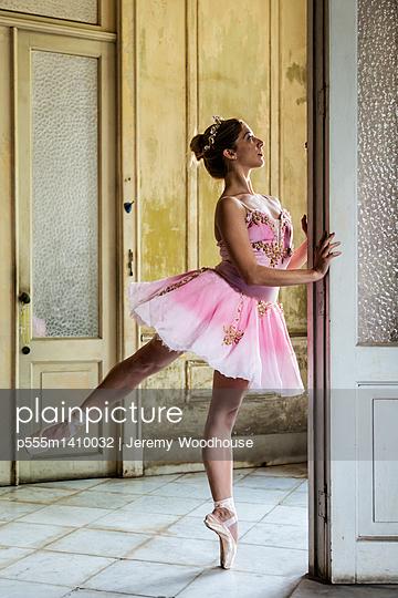 Hispanic ballet dancer posing in dilapidated mansion