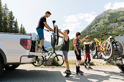 Friends unloading mountain bikes from pickup truck at sunny lakeside - p1192m2129191 by Hero Images