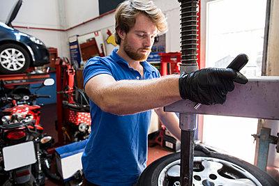 Mechanic in car workshop exchanging tire - p300m1166578 by Andrés Benitez