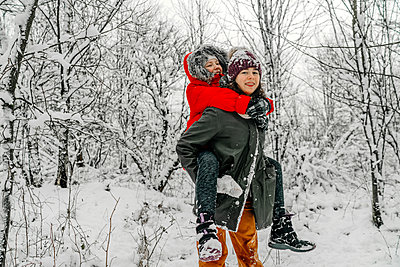 Teenage girl giving piggyback to sister against snow covered bare trees in forest - p300m2256349 by Oxana Guryanova