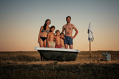 Portrait smiling family in bathing suits standing next to bathtub in rural field - p301m2070928 by Sven Hagolani