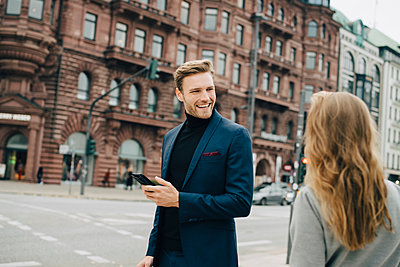 Smiling businessman with phone looking at female coworker while standing in city - p426m2186751 by Maskot