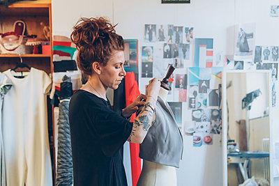 Fashion designer pinning garment onto dressmaker's dummy - p429m2058354 by Eugenio Marongiu