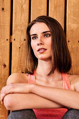 Junge Frau lehnt sich an eine Holzwand - p890m1440344 von Mielek