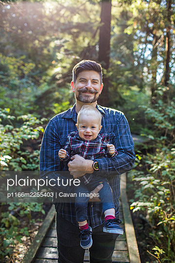 Portrait of father holding his son outdoors. - p1166m2255403 by Cavan Images