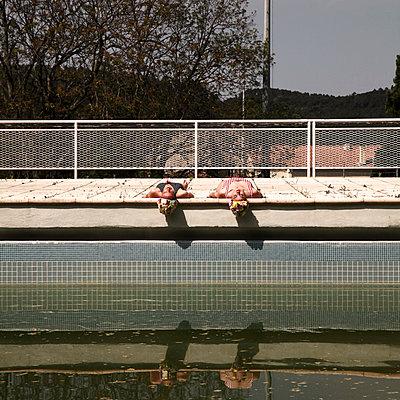 Two girlfriends sunbathing by the pool - p1105m2082590 by Virginie Plauchut