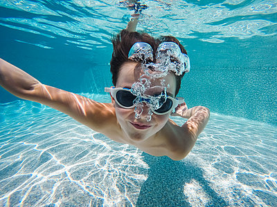 Underwater image of boy swimming in a pool with goggles on. - p1166m2201865 by Cavan Images