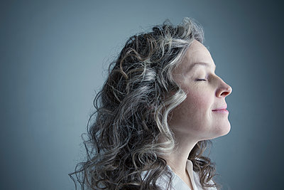 Profile portrait serene Caucasian mature woman with curly gray hair and eyes closed - p1192m1213214 by Hero Images