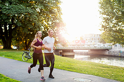 Couple jogging on footpath at park during sunrise - p426m1226338 by Kentaroo Tryman