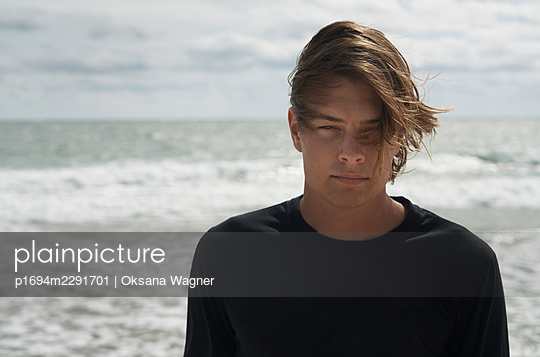 Young man with tousled hair standing in front of an ocean on a windy day - p1694m2291701 by Oksana Wagner