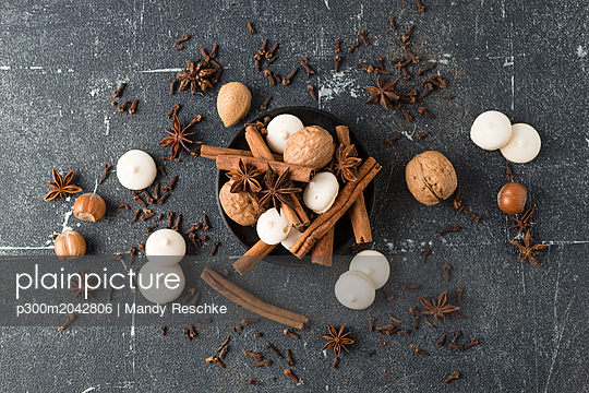 Spices, nuts and aniseed biscuit on grey ground - p300m2042806 by Mandy Reschke