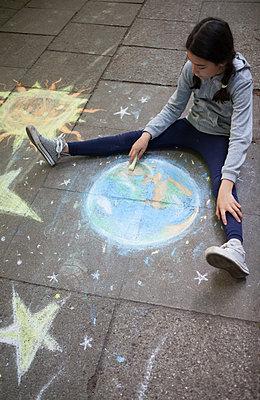 Mädchen malt Erde mit Kreide auf Gehweg - p045m1588901 von Jasmin Sander