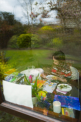 Girl painting in window at home - p1023m2208305 by Tom Merton