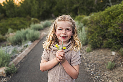 Portrait of smiling girl holding flowers while standing on road against trees in forest - p1166m2025034 by Cavan Images