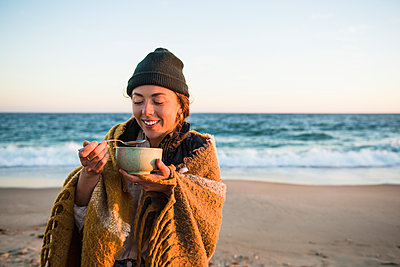Young woman enjoying bowl of soup while beach car camping in fall - p1166m2285585 by Cavan Images