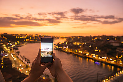 Woman's hands holding smartphone with a photo of panoramic view of Porto at sunset, Portugal - p300m2139572 by Hernandez and Sorokina