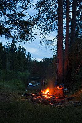 Sweden, Vastmanland, Svartalven, Man by bonfire on riverbank - p352m1100415f by Gustaf Emanuelsson