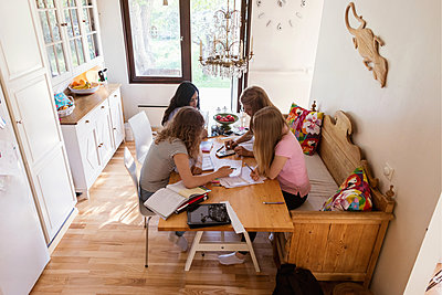 High angle view of teenage girls studying in living room - p426m1196495 by Maskot