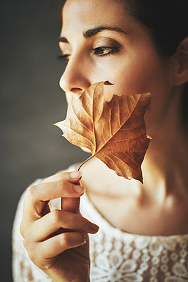 Woman holding withered leaf - p968m2020214 by roberto pastrovicchio