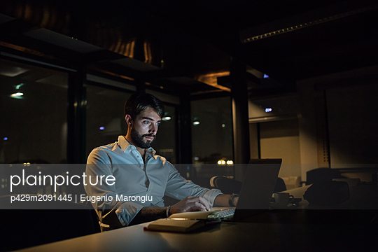 Mid adult businessman in office at night typing on laptop - p429m2091445 by Eugenio Marongiu
