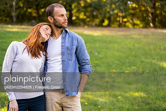 Smiling young couple enjoying a stroll in a park - p623m2294828 by Frederic Cirou