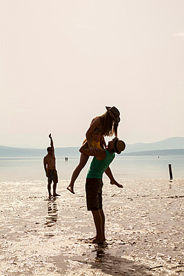 Croatia, Young couple on beach fooling about - p1026m762664f by Dario Secen
