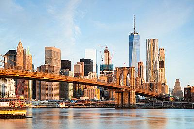 Brooklyn Bridge over East river against sky in New York city - p1166m1230525 by Cavan Images