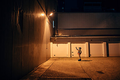 Spaceman standing under lamp at a yard at night - p300m2043147 by Vasily Pindyurin