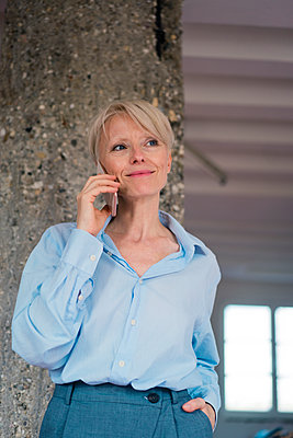 Smiling businesswoman talking on mobile phone while standing against column - p300m2267789 by Robijn Page