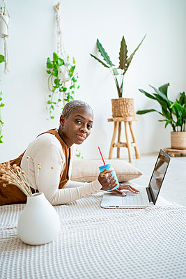 Businesswoman having juice while lying in front of laptop at home - p300m2276376 by Rafa Cortés