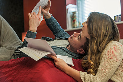 Couple lying on bed reading paperwork - p429m1027728f by Colin Hawkins