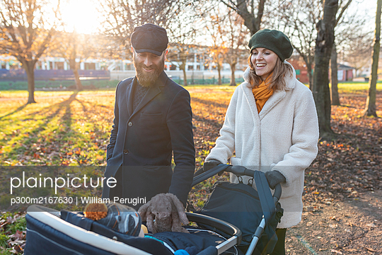 Happy couple with little son in a pushchair at park - p300m2167630 by William Perugini