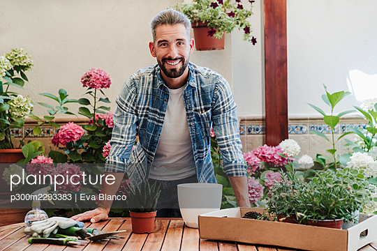 Smiling man with plants on table at backyard - p300m2293383 by Eva Blanco