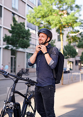 Bicycle courier puts on bike helmet - p1124m2053010 by Willing-Holtz