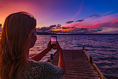 Woman with smartphone takes picture of sunset - p1455m2204888 by Ingmar Wein
