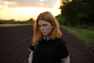 Sad young woman in a field - p1646m2229932 by Slava Chistyakov