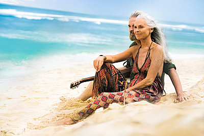 Senior hippie couple with guitar relaxing on the beach - p300m2083987 by Steve Brookland