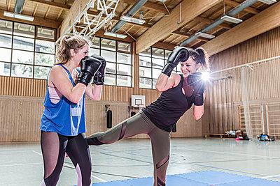 Female kickboxers practising in sports hall - p300m2144514 von Stefanie Baum