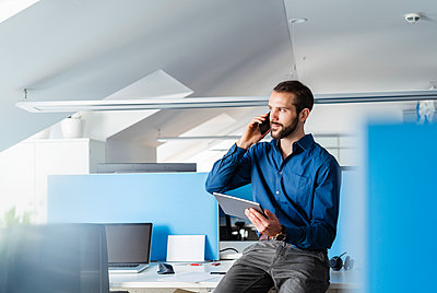 Professional with digital tablet talking on mobile phone while sitting at office - p300m2265073 by Daniel Ingold