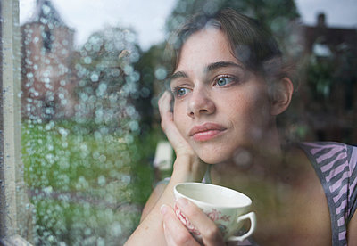 Young woman looking out of a window - p586m933112 by Kniel Synnatzschke