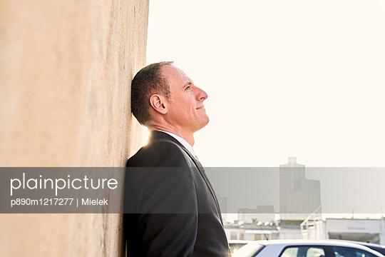 Geschäftsmann lehnt an einer Mauer - p890m1217277 von Mielek