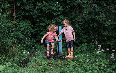 Full length of siblings playing with water by wooden post amidst plants at park - p1166m2024992 by Cavan Images