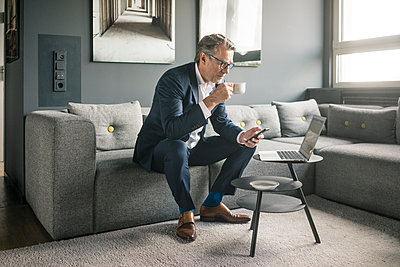 Mature businessman with cup of coffee and laptop using cell phone on couch - p300m2005569 by Joseffson