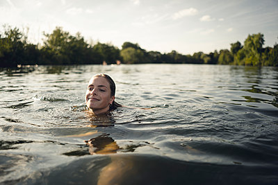 Young woman swimming in lake in summer, smiling - p300m2114296 by Gustafsson