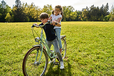 Siblings enjoying bicycle ride on grass during sunny day - p300m2197363 by Stefanie Aumiller