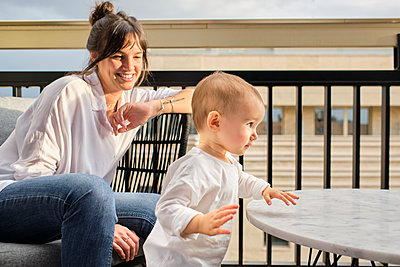 Mother spending time with toddler on balcony - p300m2250407 by Antonio Ovejero Diaz