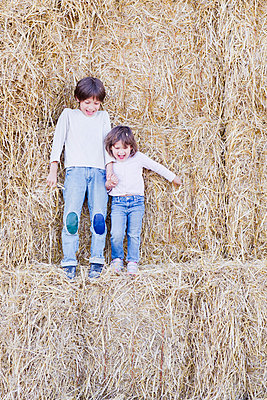 Young siblings standing on hay bales, holding hands - p675m922871 by Frederic Cirou