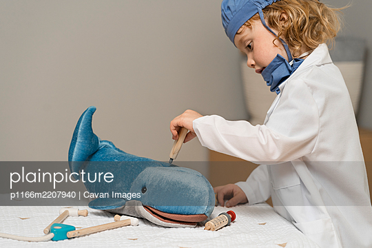 young child wearing medical PPE examines a plush toy whale by taking its temperature with a thermometer - p1166m2207940 by Cavan Images