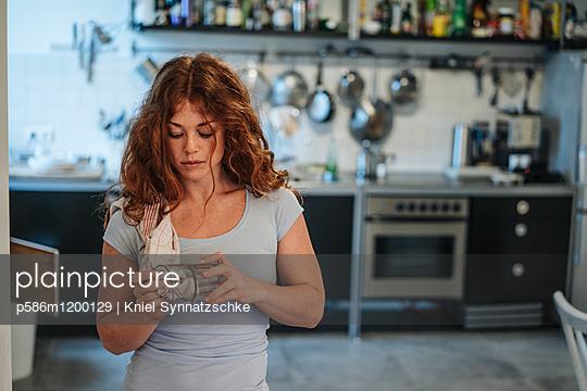 Junge Frau trocknet ein Glas ab - p586m1200129 von Kniel Synnatzschke