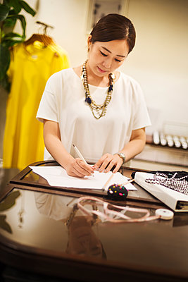 Woman working in a fashion boutique in Tokyo, Japan, writing. - p1100m1185820 by Mint Images